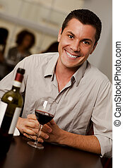 Young man with a glass of wine in a restaurant
