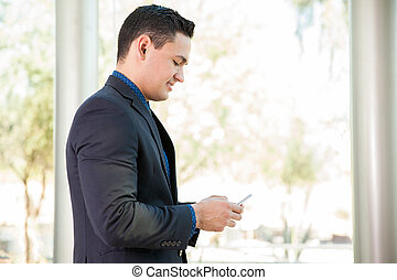 Writing emails on a cell phone - Handsome young man in a...