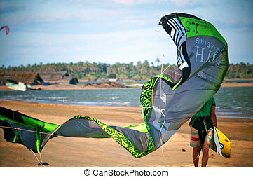 Man Carrying a Kite and Kiteboard