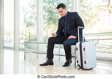 Checking flight status online - Attractive businessman using...