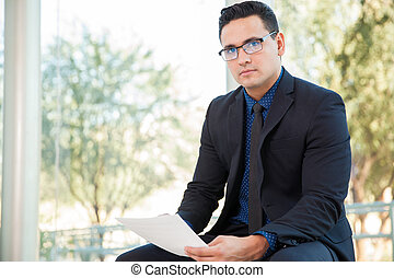 Reviewing a business contract - Hispanic young businessman...