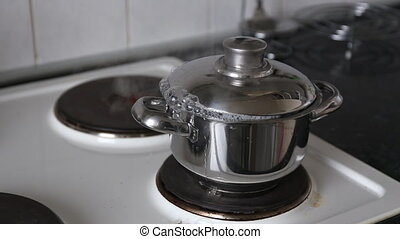 Cooking potatoes in pot with lid The water is boiling and...