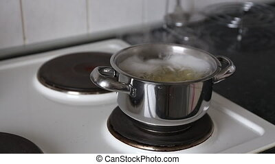 Cooking potatoes in boiling water. The water is boiling and...