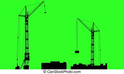 Silhouette of two cranes working on the building Green...