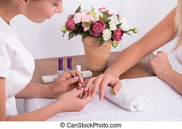 client and manicurist in manicure salon - client having...