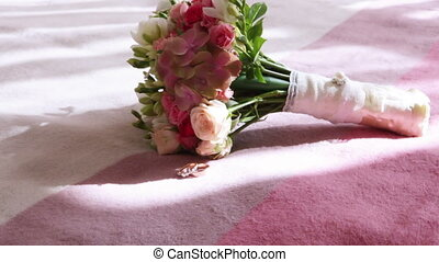 Wedding bouquet with rings - Lying on bed next to bridal...