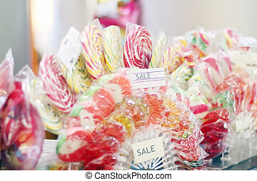 Many sweet multicolored lollipops for children in shop.