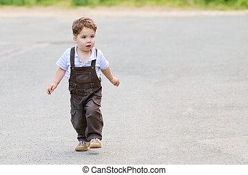 Cute beautiful little boy in brown suit, walks on asphalt road