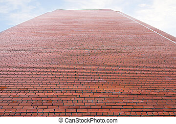 Very high wall of red brick building and cloudy sky high...
