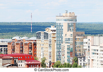 Modern buildings on edge of large city on sunny day with forest