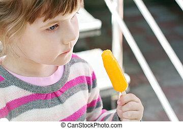 Little beautiful girl eats orange ice cream, focus on ice cream
