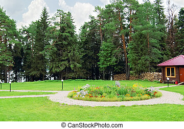 Glade with cobbled paving paths and beautiful flower bed and...