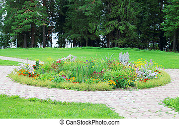Beautiful flower bed in park with paved paths and green...