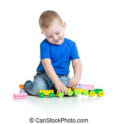 Kid boy playing with train toy sitting on white background
