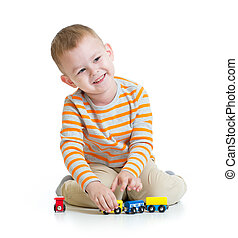 Happy kid boy playing with train toy isolated on white