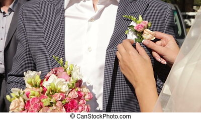 Groom boutonniere - Couple's hands next to a beautiful...