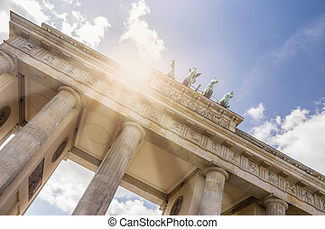 brandenburger tor with sunbeams and cloudy sky
