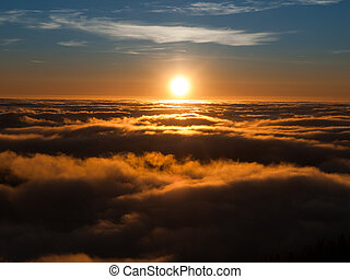 Sunset above clouds with winter mountain inversion