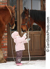 Little girl and two horses standing near the cottage door in...