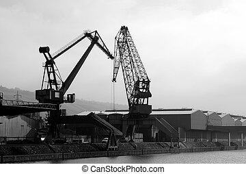 Two big cargo cranes at harbor in bw