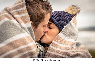 Young couple kissing outdoors under blanket in a cold day -...