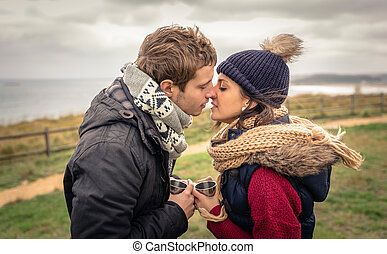 Young couple kissing and holding cups of hot drink outdoors...