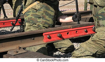 Soldiers with ak-47 and wrench are fixing nuts on the railroad.