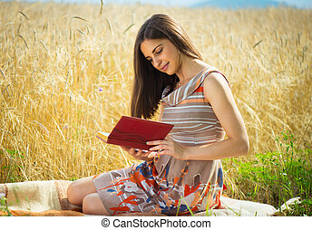 Beautiful young girl reading book at grain field