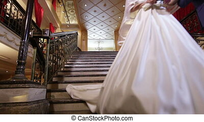 Newlyweds down stairs - Beautiful granite stairs descend...