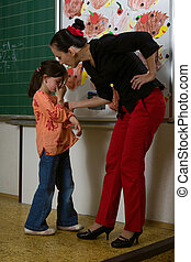 Sad girl and angry teacher - Children at school with teacher...