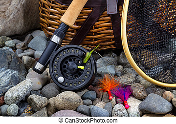 Fishing Gear on River Bed Rocks - Close up of fishing fly...