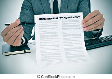young man showing a confidentiality agreement document - a...