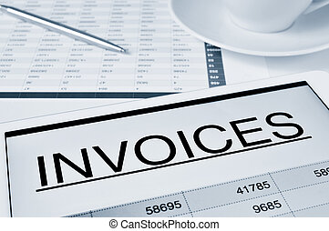 checking the invoices - closeup of a desk with a cup of...
