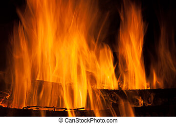 Fire, tongues of flame rise over firewood
