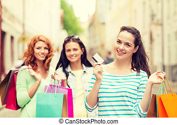 smiling teenage girls with shopping bags on street -...