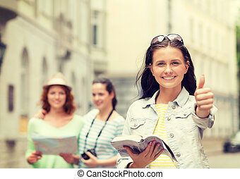 smiling teenage girls with city guide and camera - tourism,...