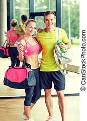 smiling couple with water bottles in gym - sport, fitness,...