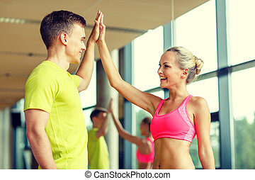 smiling man and woman making high five in gym - sport,...