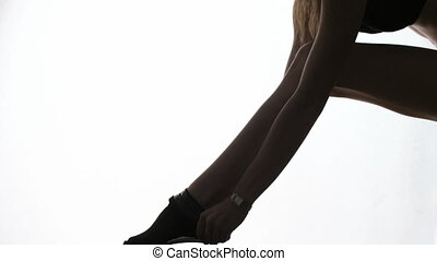 lady puts on stockings in silhouett - leg of a model putting...