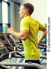 smiling man exercising on treadmill in gym - sport, fitness,...