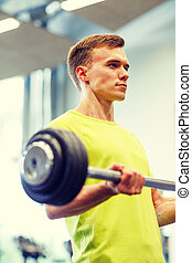 man doing exercise with barbell in gym - sport, fitness,...