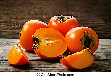 persimmon on a dark wood background. tinting. selective...