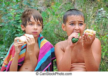 kids having dinner outdoor - two wet boys having snack...