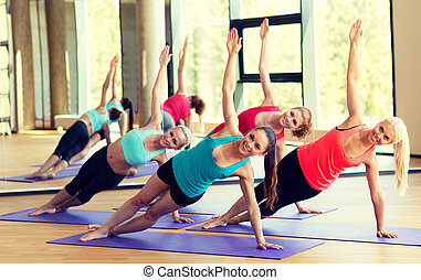 smiling women meditating on mat in gym - sport, meditation...