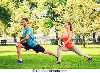 smiling couple stretching outdoors - fitness, sport,...