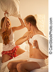 Pillow fight - Young happy couple and pillow fight in bed