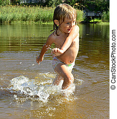 Little girl in water on sunny day - Happy smiling Little...