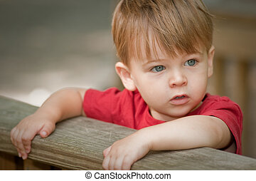 two year old boy in red shirt out side