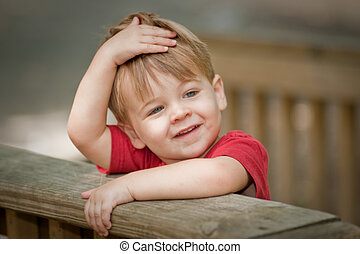 two year old boy smiling with hand on head