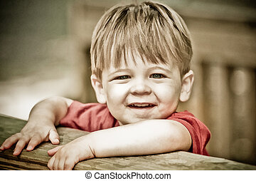 two year old boy smiling at camera with painterly effect